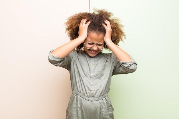 ストレスと欲求不満を感じて、頭に手を上げて、疲れて、不幸に感じて、平らな壁に片頭痛を感じる少女