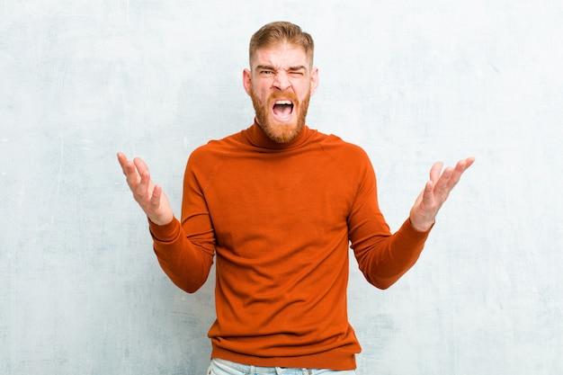 タートルネックを身に着けている若い赤い頭の男が猛烈に叫び、ストレスを感じ、空中で手を挙げてイライラして、なぜ私はコンクリートの壁に反対しているのかと言いました