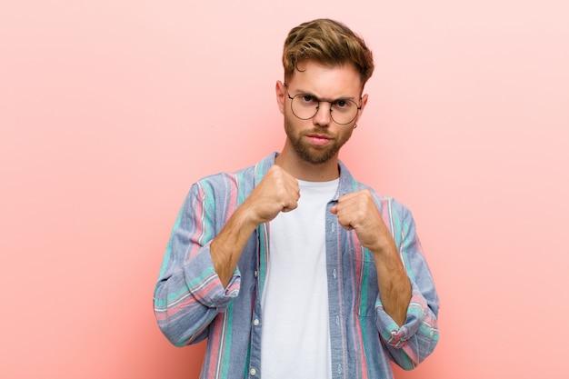 ピンクの壁に対してボクシングの位置で戦う準備ができている拳で自信を持って、怒って、強くて攻撃的な若い男