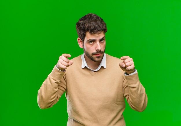 Молодой предприниматель, указывая вперед на камеру с обоими пальцами и злой выражение против зеленой стены