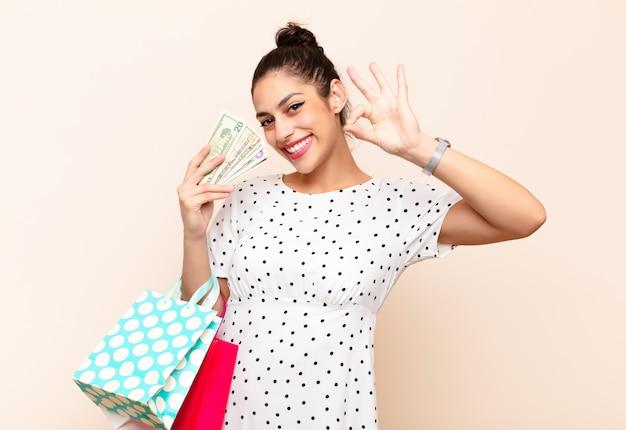 Молодая милая женщина показывая одобренный знак держа деньги и примечания доллара