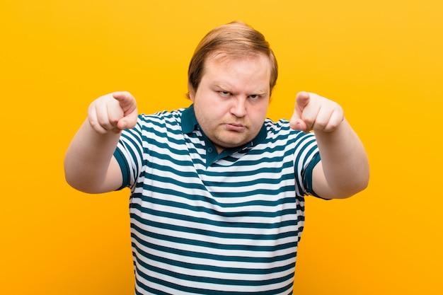 Молодой человек большого размера, указывая вперед с обоими пальцами и сердитым выражением