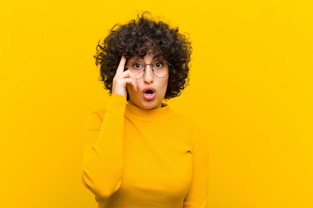 Молодая симпатичная афро женщина смотрит удивленно, с открытым ртом, в шоке, понимая новую мысль