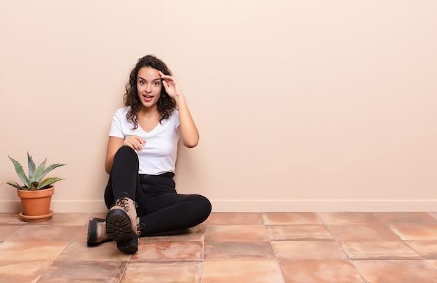 幸せ、びっくり、驚いて、笑顔でテラスの床に座っている驚くべき、信じられないほどの良いニュースを実現している若いきれいな女性