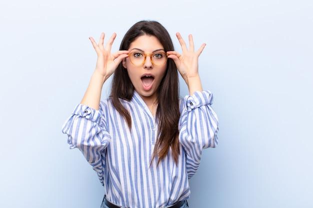 驚いた、信じられないような表情でメガネを保持しているショックを受けた若いきれいな女性