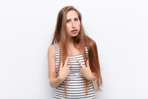 混乱し、いぶかしげな表情で自分を指している若いブロンドの女性