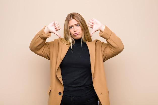 悲しい、失望した、または怒っている、親指を下に見ている若いブロンドの女性