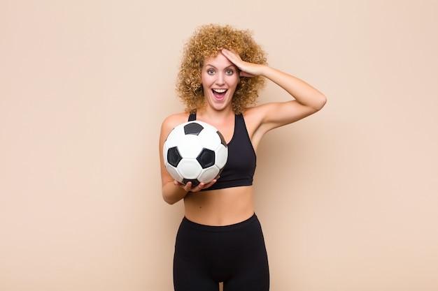 幸せそうに見えてびっくりして驚いてボールを持って若いアフロ女性