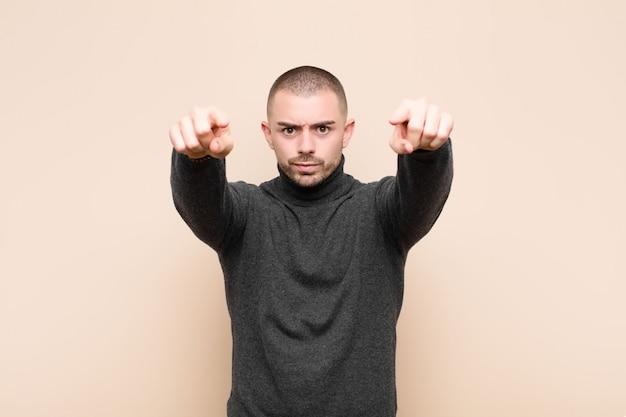 Молодой красивый мужчина, указывая вперед с обоими пальцами и сердитым выражением, говоря вам, чтобы выполнить свой долг против плоской стены