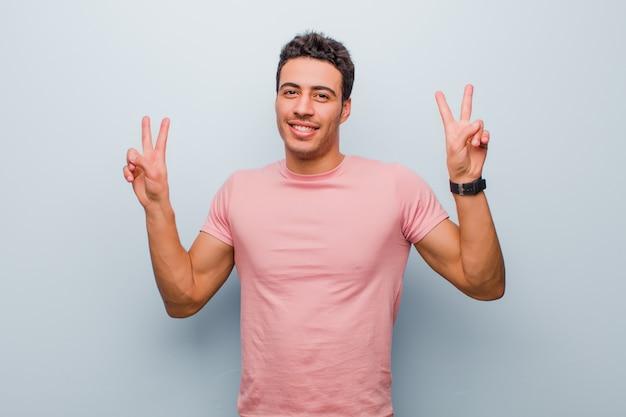 笑顔と幸せ、フレンドリーで満足している灰色の壁に両手でジェスチャーの勝利を探している若いアラビア人