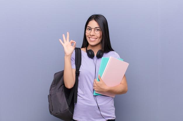 灰色の壁に対して若いかなりラテン学生女性