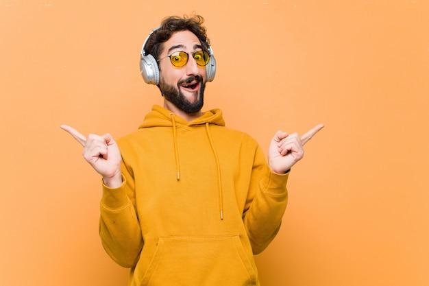 Музыка молодого сумасшедшего холодного человека слушая с наушниками против оранжевой стены