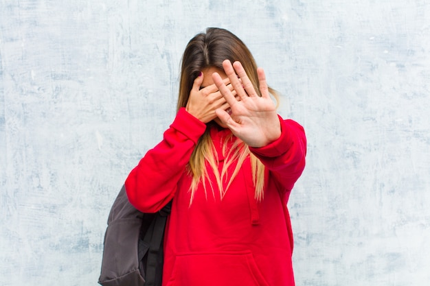 顔を手で覆い、他の手を前に置いてカメラを停止し、写真や写真を拒否する