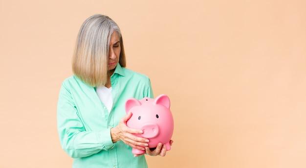 コピースペースの壁に貯金を保持している中年のきれいな女性