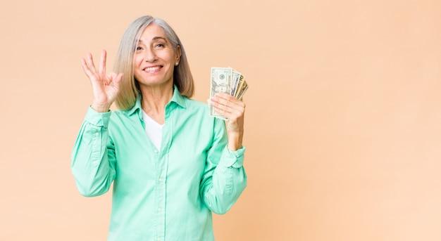 コピースペースの壁に対してドル紙幣と中年のきれいな女性