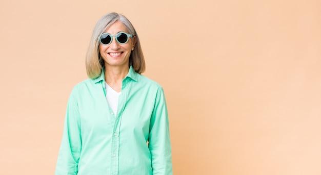 コピースペースの壁にサングラスをかけている中年のきれいな女性