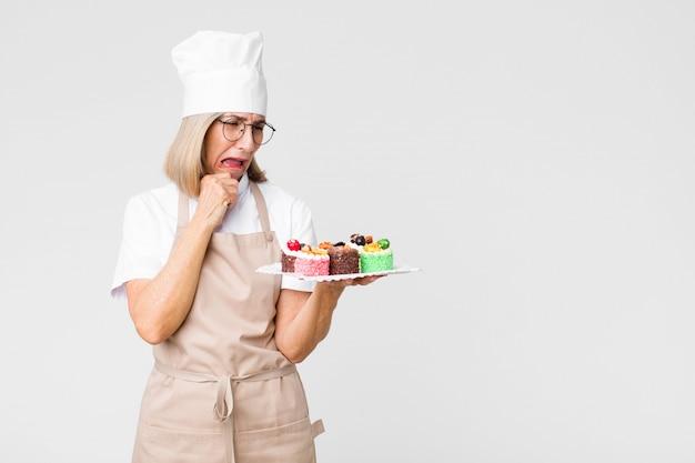 コピースペースの壁にケーキを持つ中年かなりベイカー女性