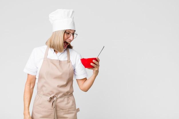 朝食ボウルを保持している中年かなりベイカー女性