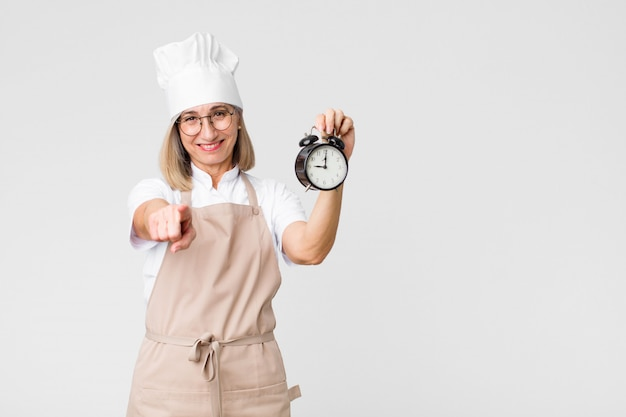 目覚まし時計を保持している中年かなりベイカー女性