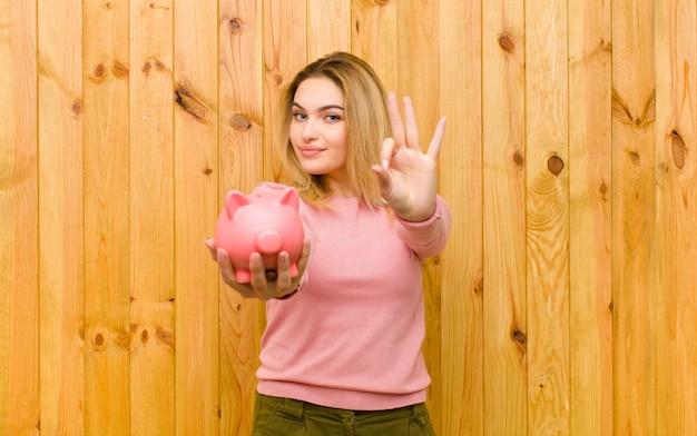 木製の壁に対して貯金を持つ若いかなりブロンドの女性