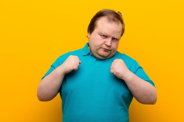 自信を持って、怒って、強くて攻撃的で、拳をボクシングポジションで戦う準備ができている