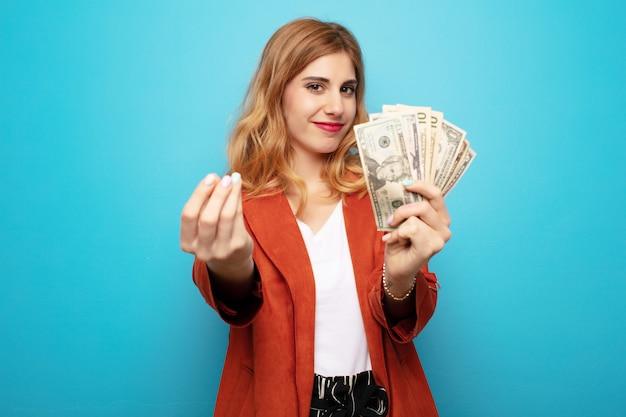 紙幣を持つ若いかなりブロンドの女性