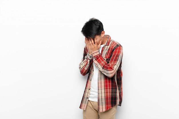 悲しみ、欲求不満の絶望、泣き、横顔で目を手で覆う