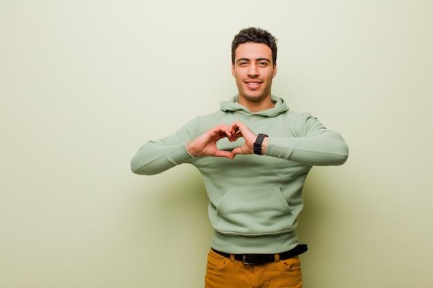 Улыбаясь и чувствуя себя счастливыми, милыми, романтичными и влюбленными, делая форму сердца двумя руками