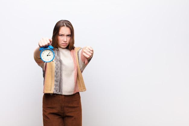 白い壁に目覚まし時計を保持している若いブロンドの女の子