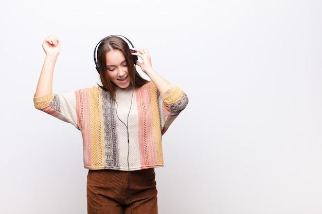白い壁にヘッドフォンで音楽を聴く若いブロンドの女の子