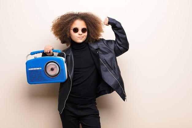 Афро-американская маленькая девочка против музыки плоской стены слушая с старомодным радио
