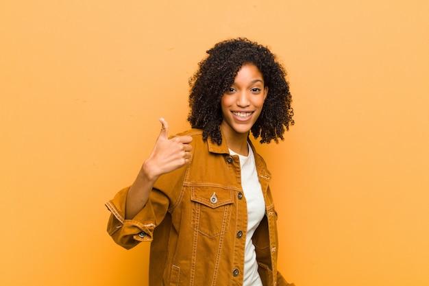 親指を現しながらポーズをとって若いアフリカ系アメリカ人女性
