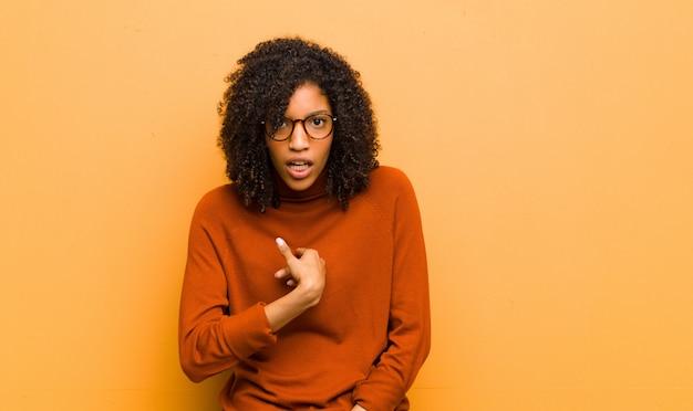 若いアフリカ系アメリカ人女性が驚いて、自分に指を指しながらポーズ