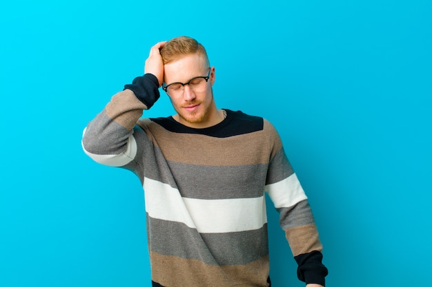 笑いと額を平手打ちのセーターで金髪の男