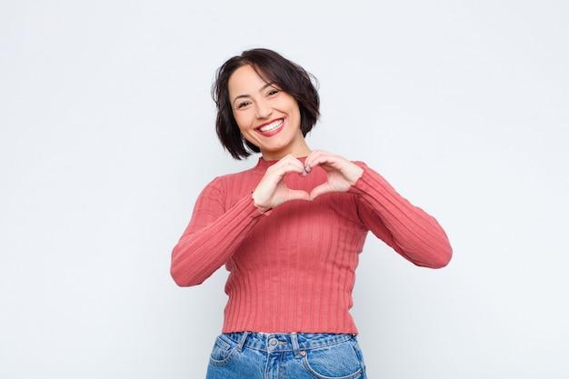Женщина улыбается и чувствует себя счастливой, милой, романтичной и влюбленной, делая форму сердца обеими руками