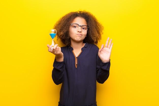 Афро-американская маленькая девочка против плоской стены, держащей таймер с песочными часами