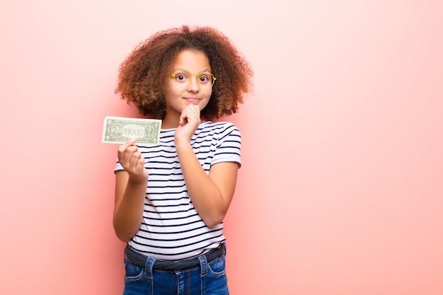 Афро-американская маленькая девочка против плоской стены с банкнотами доллара