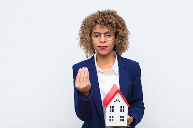 Женщина делает деньги жестом, говоря вам, чтобы оплатить свои долги!