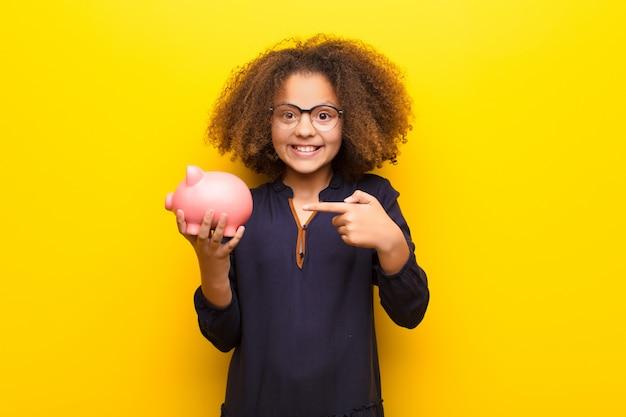 Афро-американская маленькая девочка против плоской стены, держащей копилку