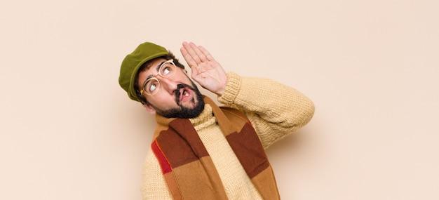 Человек выглядит серьезным и любопытным, слушает, пытается услышать секретный разговор или сплетни, подслушивая