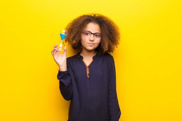 Афро-американская маленькая девочка против плоской стены, держащей песочные часы
