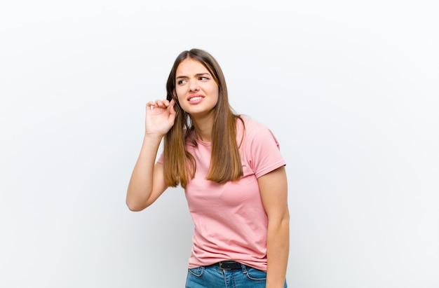 Женщина выглядит серьезной и любопытной, слушает, пытается услышать секретный разговор или сплетни, подслушивая