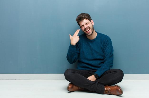 Человек смотрит несчастным и подчеркнул, самоубийство жест делает пистолет знак рукой, указывая на голову