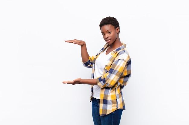Держа объект обеими руками на боковой копии, показывать, предлагать или рекламировать объект