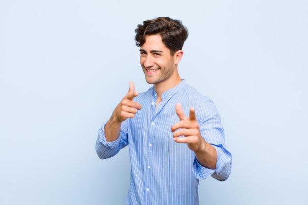Улыбающийся с положительным, успешным, счастливым отношением, указывающим вперед, делая знак оружия руками