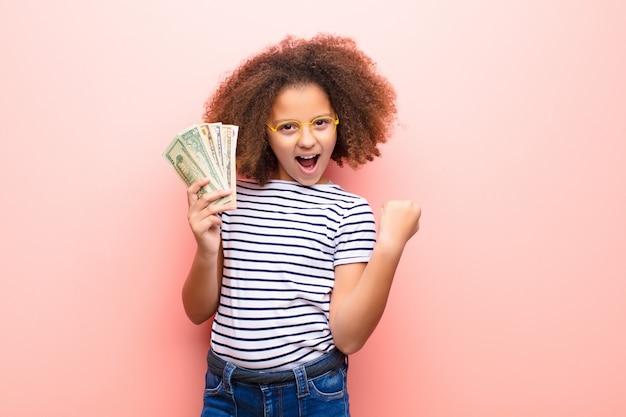ドル紙幣と平らな壁に対してアフリカ系アメリカ人の女の子