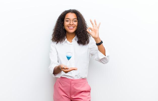 白い壁に砂のタイマー時計を持つ若いかなり黒人女性
