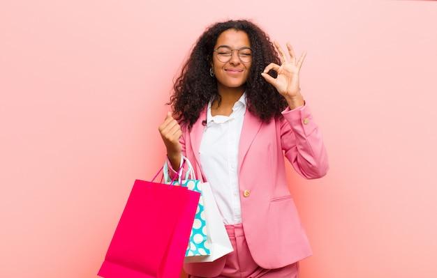 Молодая черная милая женщина с хозяйственными сумками против розовой стены