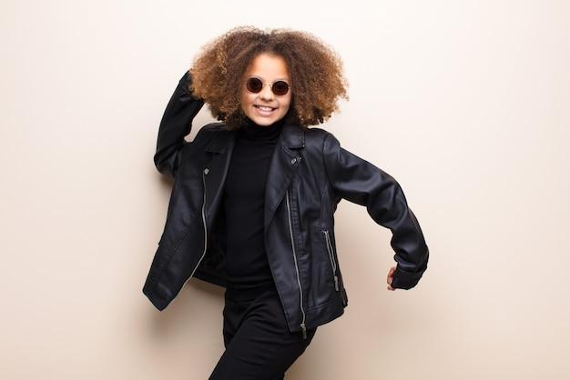 Афро-американская маленькая девочка против плоской стены. классная концепция