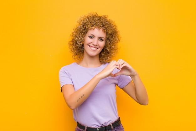 Улыбаться и чувствовать себя счастливым, милым, романтичным и влюбленным, делая форму сердца обеими руками